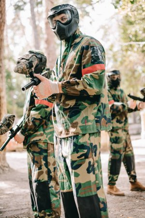male paintball player in uniform and goggle mask looking at camera and standing with his team outdoors