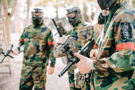 partial view of paintball team in camouflage and protective masks standing with paintball guns outdoors