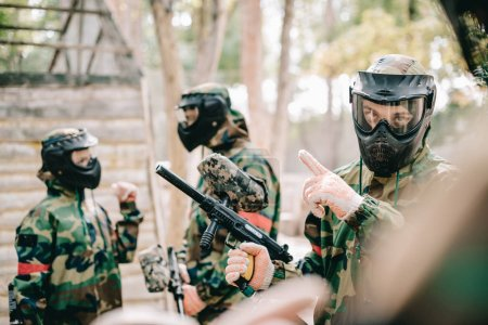 male paintball player in goggle mask with marker gun pointing by finger to his team outdoors