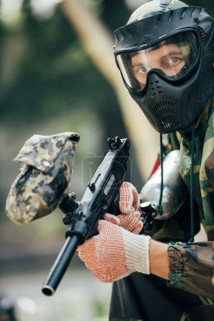 male paintball player in goggle mask and camouflage with paintball gun outdoors