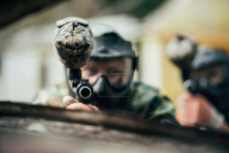 selective focus of paintball team in uniform and protective masks aiming by paintball guns outdoors