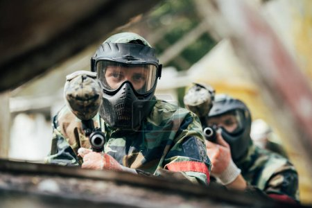 male paintballer and his team in uniform and protective masks aiming by paintball guns outdoors