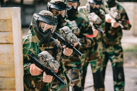 selective focus of female paintball player holding marker gun with her team in protective masks and camouflage playing paintball outdoors