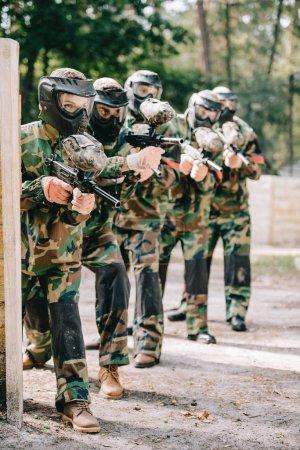 Photo pour Joueuse de paintball tenant un pistolet marqueur avec son équipe dans des masques de protection et de camouflage jouant au paintball à l'extérieur - image libre de droit