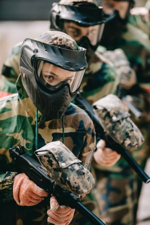 portrait of female paintball player holding marker gun with her team in protective masks and camouflage playing paintball outdoors
