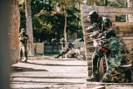 Photo for Paintball players in camouflage and protective masks aiming with marker guns and hiding behind wooden wall outdoors - Royalty Free Image