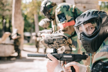 portrait of male paintball player in protective mask holding marker gun and looking at camera outdoors
