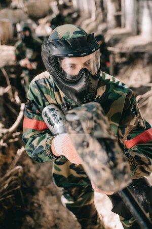 Photo pour Foyer sélectif du joueur de paintball masculin en masque de masque et camouflage visant par pistolet de paintball de fossé à l'extérieur - image libre de droit