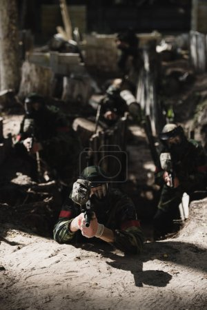 Photo for Paintball team in camouflage and protective masks aiming by marker guns from ditch outdoors - Royalty Free Image