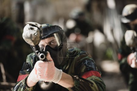 Photo for Selective focus of serious male paintball player in goggle mask and camouflage aiming by paintball gun outdoors - Royalty Free Image