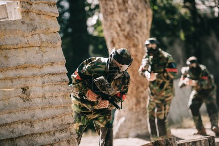 selective focus of paintball player in protective mask holding marker gun looking out of wooden wall outdoors
