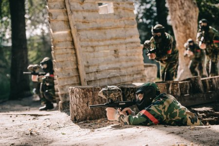paintball player laying on ground and aiming by marker gun while his team hiding behind wooden wall outdoors