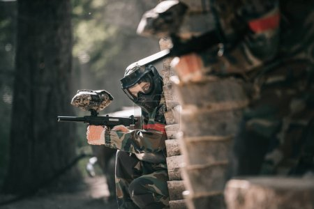selective focus of paintball player in protective mask holding marker gun and his teammate hiding behind wooden wall outdoors