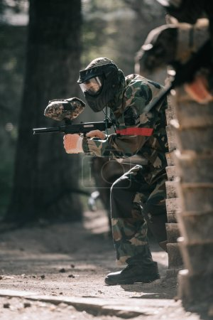 selective focus of male paintball player in goggle mask and camouflage aiming by paintball gun outdoors