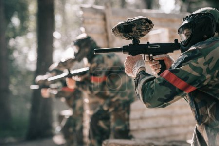 selective focus of paintball player in goggle mask aiming with marker gun and his team on background outdoors