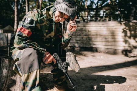 smiling young female paintballer in camouflage uniform sitting with paintball gun outdoors