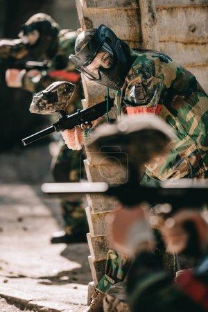 Foto de Enfoque selectivo del jugador de paintball femenino en camuflaje y máscara protectora con pistola marcador al aire libre - Imagen libre de derechos