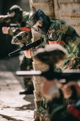 selective focus of female paintball player in camouflage and protective mask holding marker gun outdoors