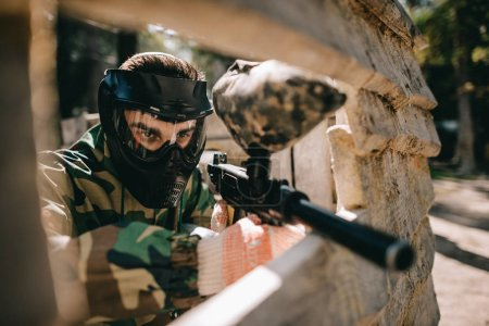 concentrated male paintball player in goggle mask and camouflage aiming by paintball gun outdoors