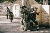 male paintball players in camouflage and protective masks hiding behind tree and shooting by marker guns outdoors
