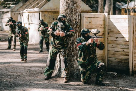 paintball players wearing camouflage and goggle masks shooting by markers guns near tree and their team on background outdoors