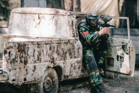 male paintball player in goggle mask and camouflage aiming by paintball gun from broken car outdoors