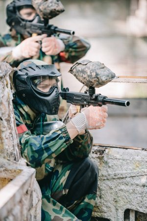 side view of concentrated paintball player in protective mask aiming with marker gun outdoors