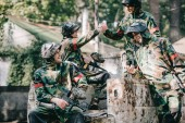 happy paintball team in camouflage celebrating victory and shaking hands on broken car outdoors