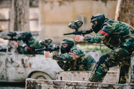 paintball players in camouflage and protective masks aiming with marker guns from broken car outdoors