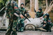 cropped image of paintball team in camouflage uniform with marker guns resting near broken car outdoors