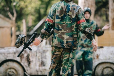 partial view of paintball players in camouflage uniform resting near broken car outdoors