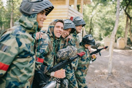 selective focus of happy paintball players in camouflage with marker guns embracing each other outdoors