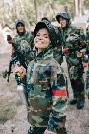 attractive smiling female paintballer in uniform holding paintball gun while her team standing behind outdoors
