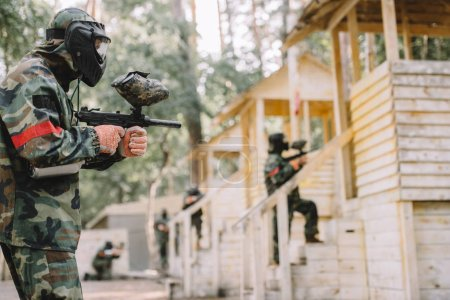 side view of paintballer in camouflage and protective mask aiming by marker gun while his team standing behind outdoors