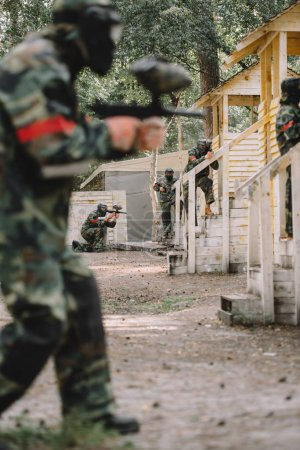 selective focus of paintballer in camouflage and protective mask aiming by marker gun while his team standing behind outdoors