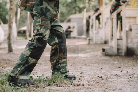cropped image of paintball player wearing camouflage uniform outdoors