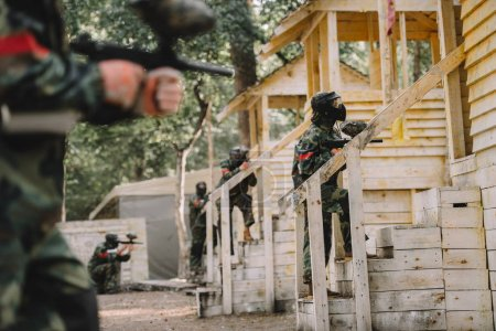 paintball team in uniform and protective masks standing on staircase of wooden towers with paintball guns outdoors