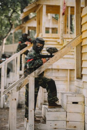 female paintballer in camouflage and goggle mask with marker gun standing on staircase of wooden tower outdoors