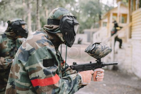 Photo for Side view of male paintballer and his team in uniform and protective masks aiming by paintball guns outdoors - Royalty Free Image