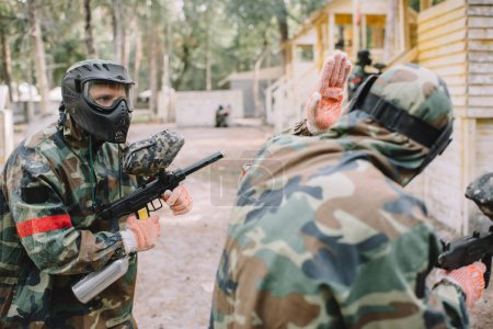 rear view of paintball player in camouflage uniform doing follow me gesture to his team outdoors