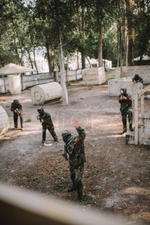 high angle view of paintball player in uniform doing follow me gesture to his team with paintball guns outdoors