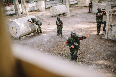 high angle view of paintball player in uniform pointing by hand to his team with markers guns outdoors