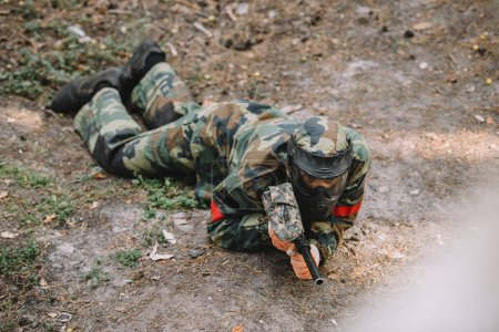 high angle view of male paintball player in goggle mask and camouflage crawling with paintball gun outdoors