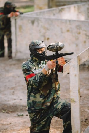 Photo for Side view of confident male paintball player in goggle mask and camouflage aiming by paintball gun outdoors - Royalty Free Image