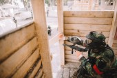 male paintball player in protective mask and camouflage uniform holding marker gun and doing follow me gesture from wooden tower outdoors
