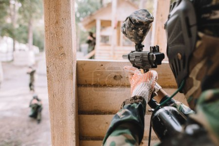 Photo for Selective focus of paintball player in camouflage uniform aiming by paintball gun from wooden tower outdoors - Royalty Free Image