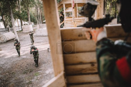 cropped image of paintball player in camouflage uniform aiming by paintball gun from wooden tower outdoors