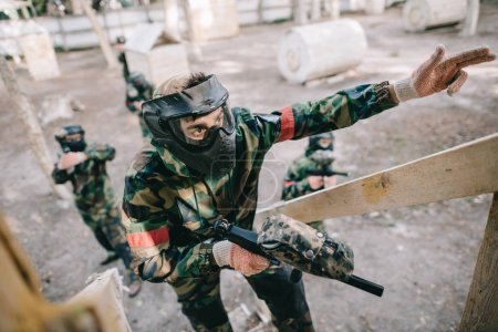 serious male paintball player in camouflage and goggle mask with marker gun pointing by fingers on staircase to histeam standing behind outdoors