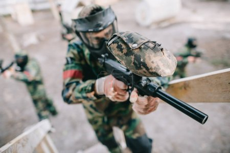 selective focus of male paintball player aiming by marker gun on staircase while his team shooting behind outdoors
