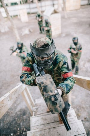 high angle view of paintball player aiming by marker gun and running on staircase while his team standing behind outdoors